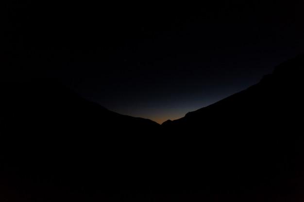 Landschaft des dunklen schattenbildhügels in der nacht mit einem licht auf ihnen