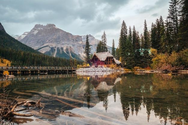 Landschaft des holzhauses mit felsigen bergen und bewölkter wehender reflexion über emerald lake im yoho-nationalpark, kanada