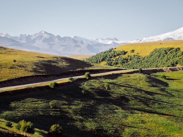 Landschaft des nordkaukasus die straße führt durch grüne hügel und felder