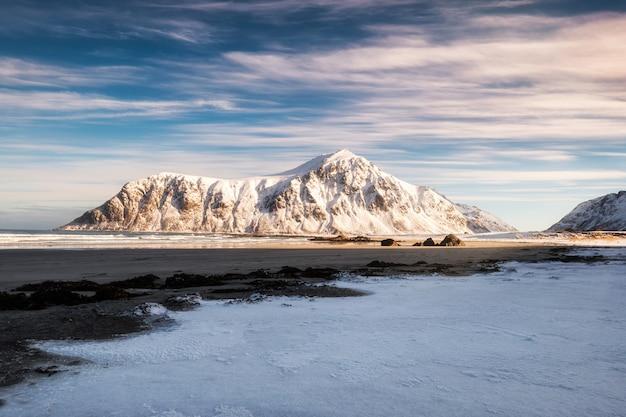 Landschaft des sonnenlichts leuchtend auf schneebedeckten gebirgszug auf küstenlinie