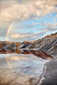 Landschaft eines regenbogens über hügeln und see