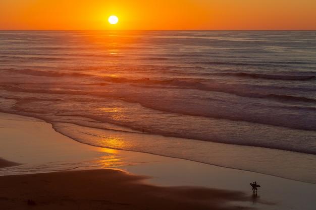 Landschaft eines schönen sonnenuntergangs, der auf meer vom strand in portugal, algarve reflektiert