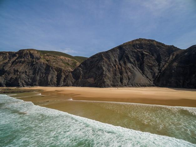 Landschaft eines strandes umgeben von hohen felsigen bergen unter einem blauen himmel in portugal, algarve