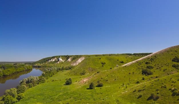 Landschaft im tal des don in zentralrussland. draufsicht auf den frühlingsküstenwald, den hügel und den teich.