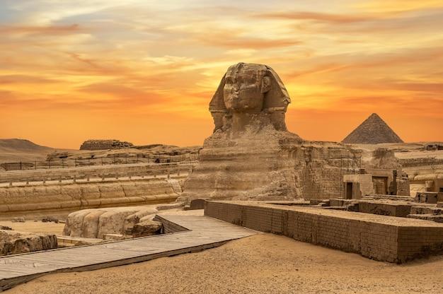 Landschaft mit ägyptischen pyramiden, großer sphinx und silhouetten alte symbole und wahrzeichen ägyptens für ihr reisekonzept nach afrika im goldenen sonnenlicht. die sphinx im pyramidenkomplex von gizeh bei sonnenuntergang
