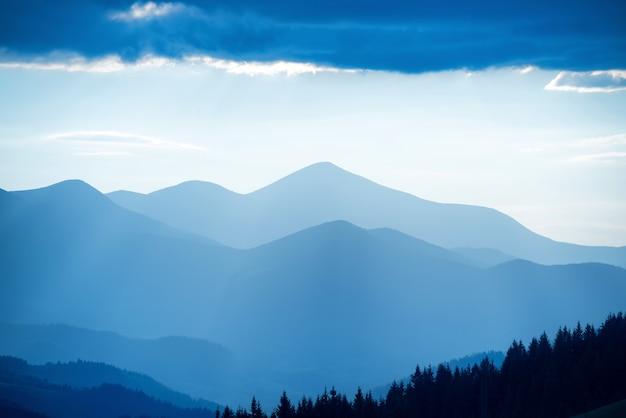 Landschaft mit blauen bergen und wald bei sonnenuntergang