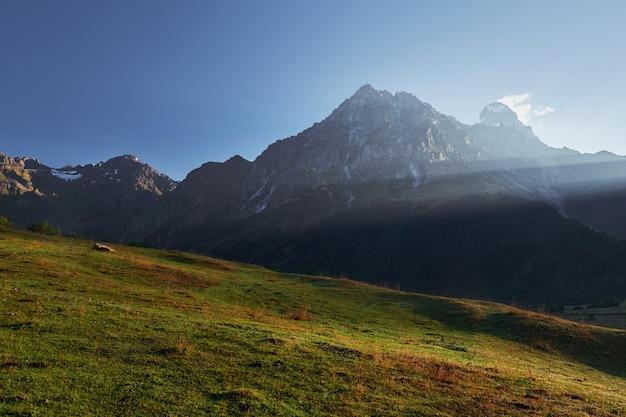 Landschaft mit blick auf die spitze des ushba-berges in den morgensonnenstrahlen