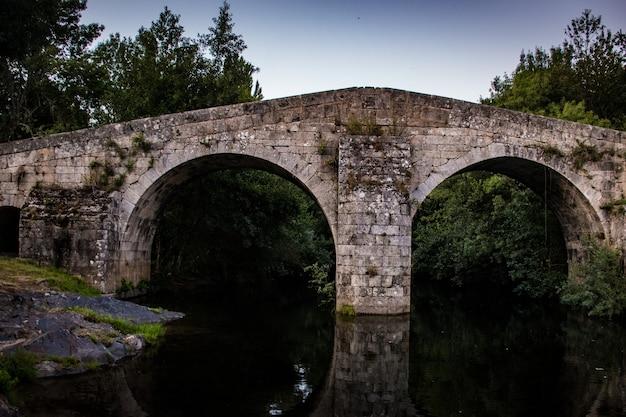 Landschaft mit einer römischen brücke über den fluss des ruhigen wassers