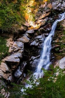 Landschaft mit fließendem frischem kühlem blauem wasser des wasserfalls in den bergen