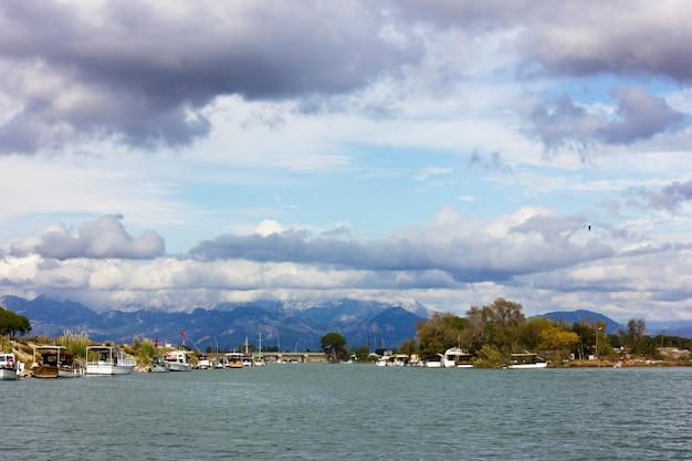 Landschaft mit fluss und bergen. große weiße cumuluswolken