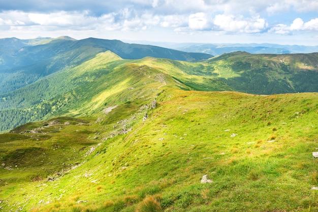 Landschaft mit grünen bergen und hügeln mit blauem himmel