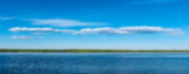 Landschaft mit himmel mit wasser und wolken mit wald am horizont