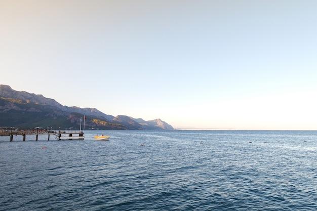 Landschaft mit meer und boot. boot in der nähe des piers. abend, sonnenuntergang sonnenlicht