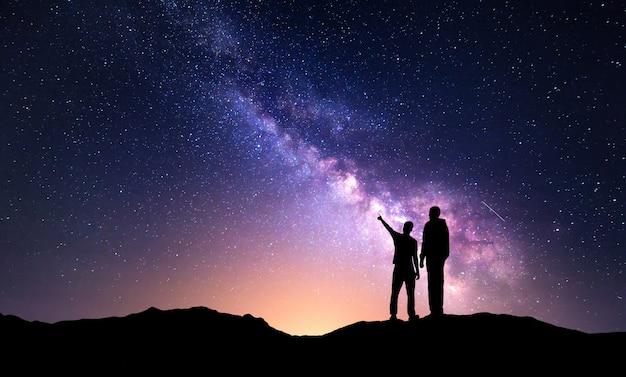 Landschaft mit milchstraße und silhouette eines vaters und eines sohnes