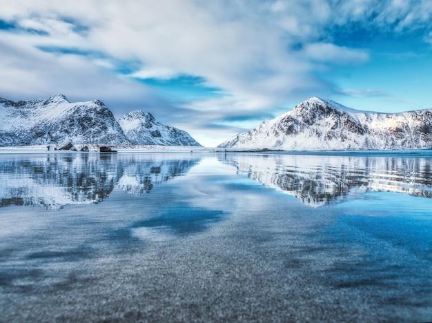 Landschaft mit schneebedeckten bergen, meer, blauem himmel mit im wasser reflektierten wolken im winter