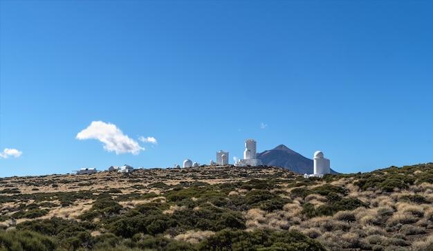 Landschaft mit sonnenobservatorium auf den bergen mit dem vulkan teide dahinter.