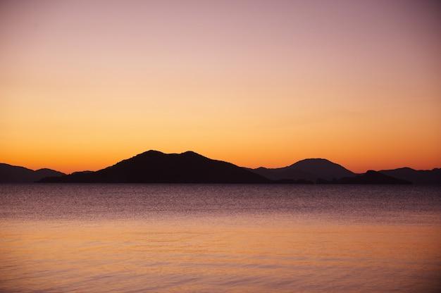 Landschaft. sonnenuntergang über den bergen und dem meer