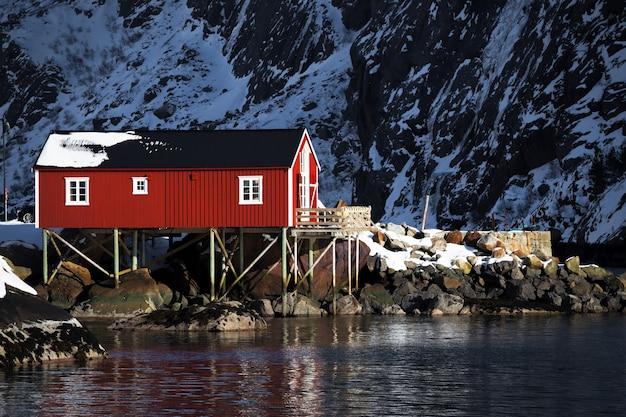 Landschaft - traditionelles norwegisches holzhaus rorbu, das am ufer des fjords und der berge in der ferne steht. norwegen.