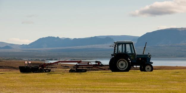 Landschaft, traktor, der landmaschine vor schroffem berg zieht