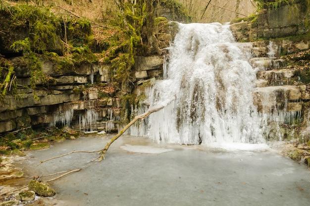 Landschaft von gefrorenem fluss und von wasserfall in einem wald von spanien