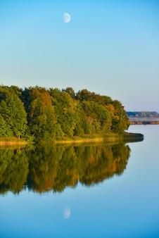 Landschaft von gelben und grünen waldbäumen des herbstes werden im wasser des sees am abend reflektiert