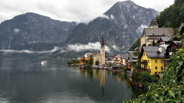 Landschaft von hallstatt, umgeben von wasser und felsigen bergen an einem regnerischen tag in österreich