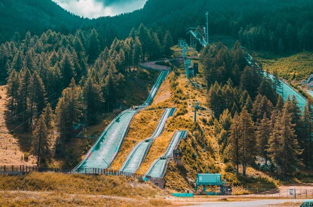 Landschaft von hohen hügeln bedeckt mit lärchen und pfaden unter bewölktem himmel in pragelato, italien
