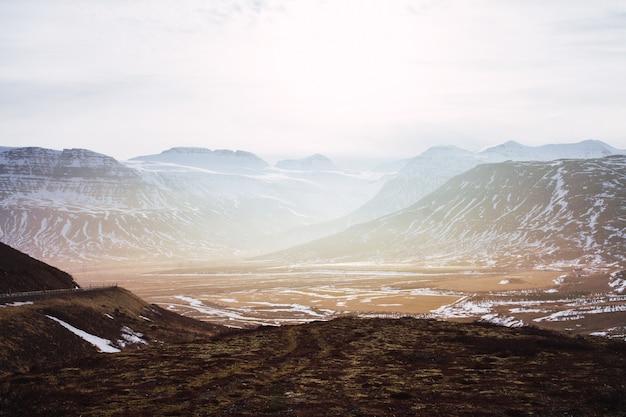 Landschaft von hügeln bedeckt im gras und im schnee unter einem bewölkten himmel und sonnenlicht in island