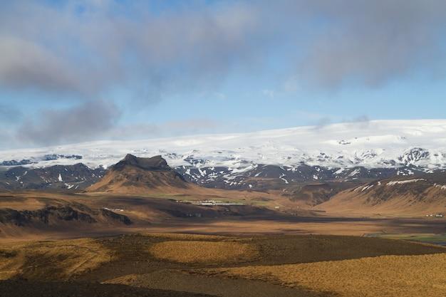 Landschaft von hügeln bedeckt im schnee unter einem bewölkten himmel und sonnenlicht in island