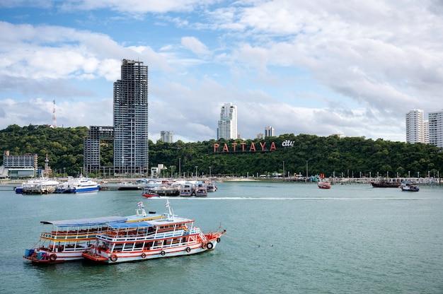 Landschaft von pattaya strand mit gebäude und fährhafen im tropischen meer bei chonburi