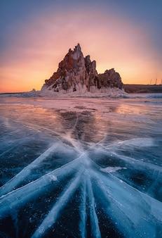 Landschaft von shamanka-felsen bei sonnenaufgang mit natürlichem brechendem eis in gefrorenem wasser auf dem baikalsee, sibirien, russland.