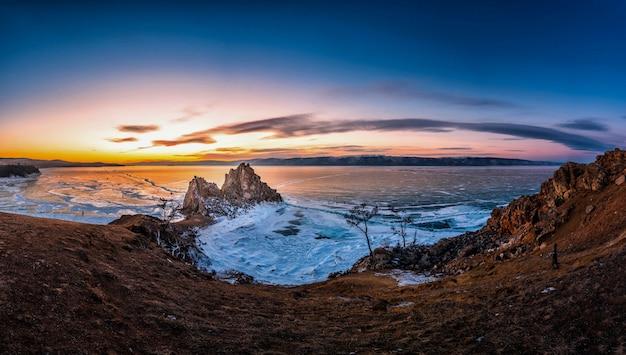 Landschaft von shamanka-felsen bei sonnenuntergang mit natürlichem brechendem eis in gefrorenem wasser auf dem baikalsee, sibirien, russland.