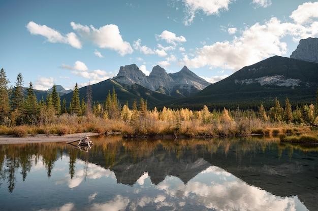 Landschaft von three sisters mountain im herbstlichen waldreflexion auf teich in canmore im banff nationalpark, kanada,
