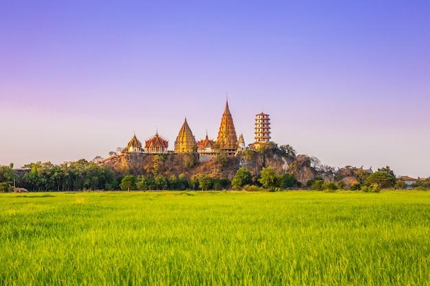 Landschaft von wat tham sua temple (tiger cave temple) im sonnenuntergang scence mit jasminreisfeldern