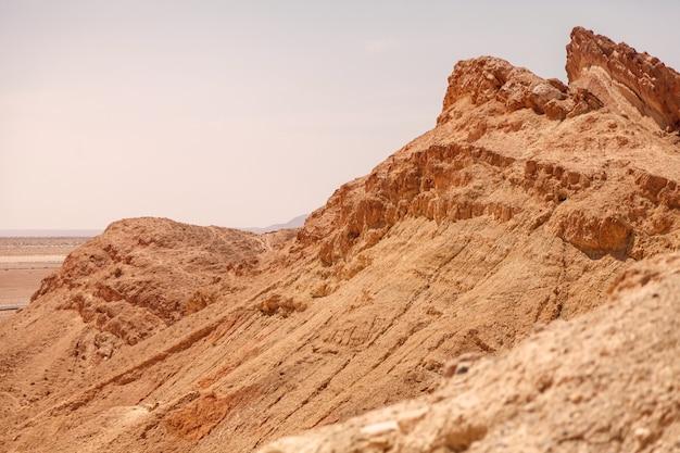 Landschafts-chebika-oase in der sahara-wüste. blick auf die berglandschaft. bergoase mit malerischer aussicht in nordafrika. das hotel liegt am fuß des jebel el negueba. atlasgebirge am sonnigen nachmittag. tozeur, tunesien