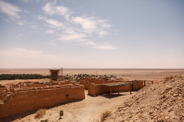 Landschafts-chebika-oase in der sahara-wüste. ruinensiedlung und palme. bergoase mit malerischer aussicht in nordafrika. das hotel liegt am fuß des jebel el negueba. atlasgebirge am sonnigen nachmittag. tozeur, tunesien
