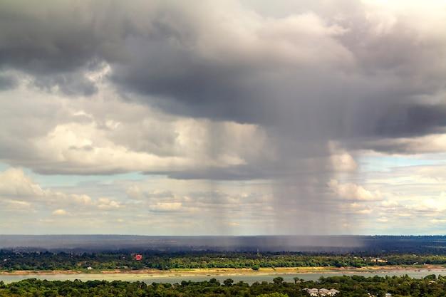 Landschafts- und regenwolkenfluß führen das feld in ländlichem von thailand.