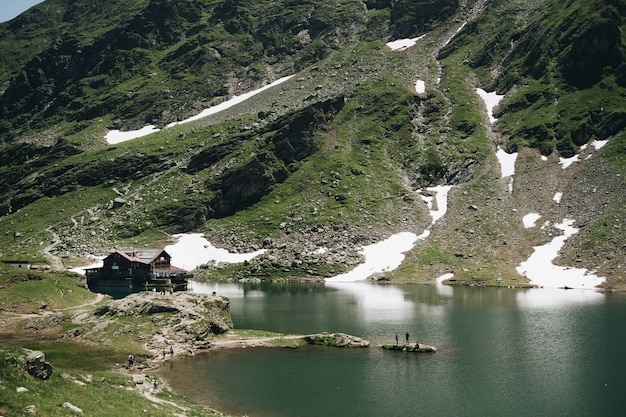 Landschaftsansicht des balea-sees in rumänien und des fagaras-gebirges im sommer mit schneebedeckten gipfeln