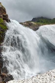 Landschaftsansicht des idyllischen wasserfalls, der in einem felsigen berg in ein schneefeld fällt