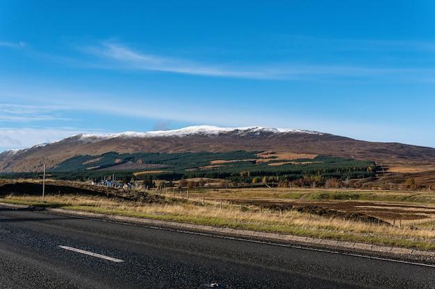 Landschaftsansicht mit dem baumbedeckten berg am horizont vom straßenrand aus gesehen