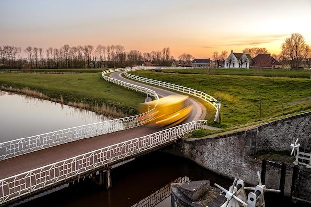 Landschaftsaufnahme einer brücke über einen kanal in einer grünen nachbarschaft