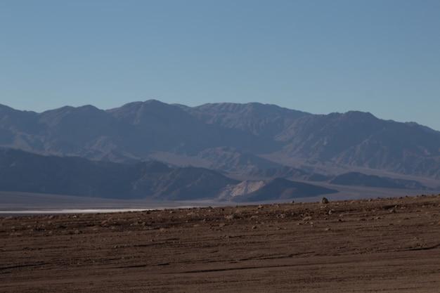 Landschaftsaufnahme eines halbtrockenen verlassenen gebiets vor einer schönen bergkette