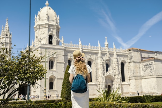 Landschaftsaufnahme eines jungen weiblichen reisenden, der die ansicht im jerónimos-kloster lissabon portugal genießt