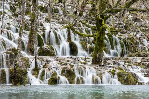 Landschaftsaufnahme eines wasserfalls, der von moosigen klippen in einen see fließt