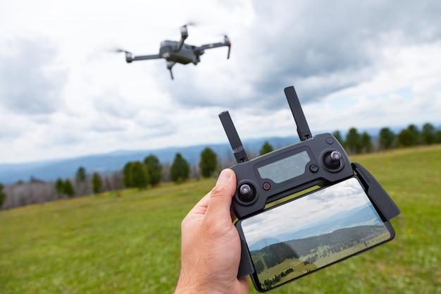Landschaftsbau auf einem quadrocopter. ein junger mann hält ein quadrocopter-bedienfeld mit einem monitor in der hand.