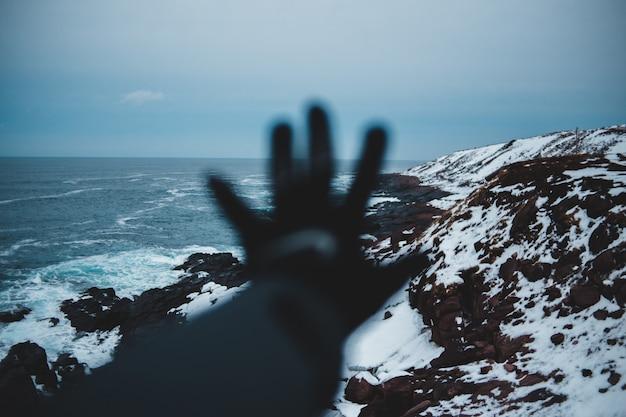 Landschaftsfotografie der klippe bedeckt mit schnee, das gewässer betrachtet