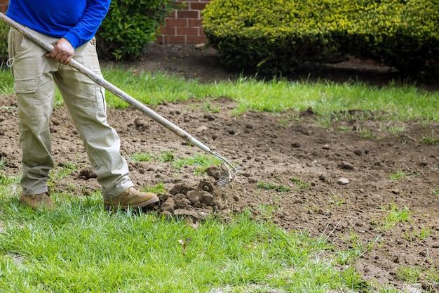 Landschaftsgärtner, die mit dem rechen rasen mähen, ist auf dem boden, gartenarbeit in der landwirtschaft