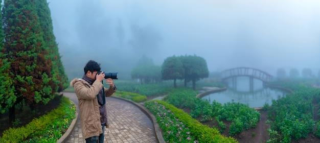 Landschaftsnebel-panoramafotograf, der bilder von nebligen gärten macht