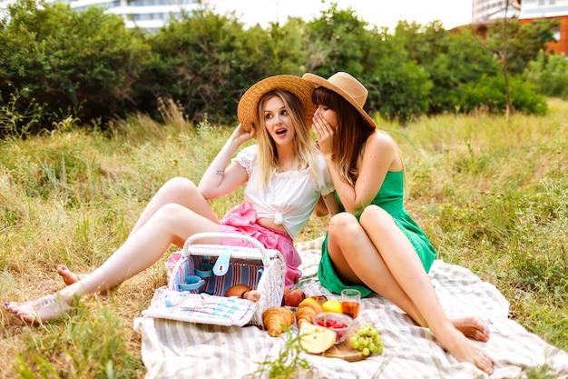 Landschaftsporträt im freien von zwei glücklichen besten freunden, die picknick genießen enjoying