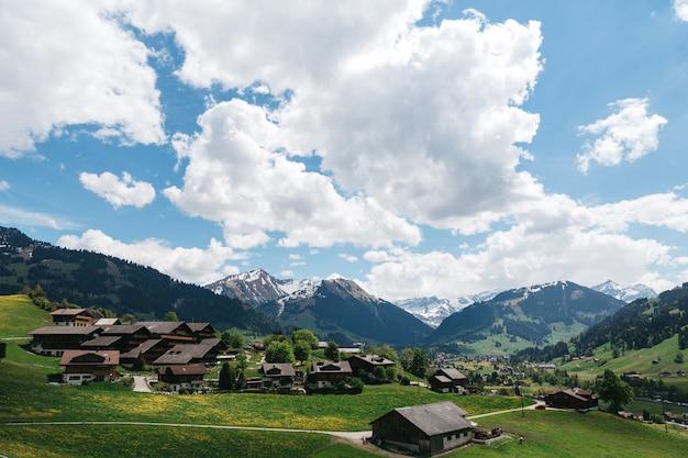Landschaftsschweizer dorf auf gebirgshintergrund